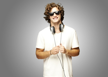 portrait of young man smiling with headphones over grey background photo