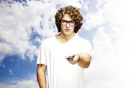 portrait of young man using tv control against a cloudy sky background Stock Photo - 11507102