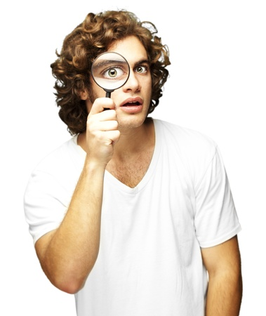 see through: portrait of young man looking through a magnifying glass against a white background Stock Photo
