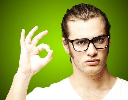 Porträt einer schönen jungen Mann zu tun Genehmigung Geste über grüne