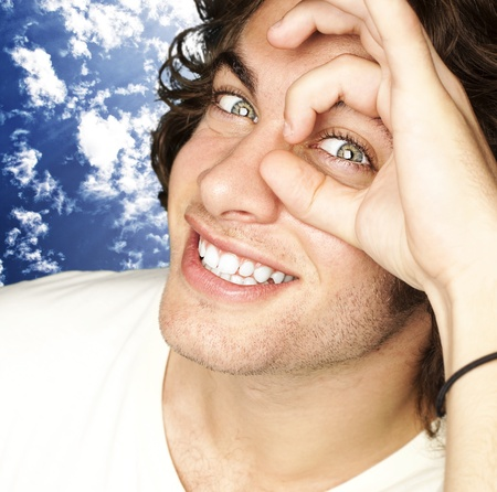 clear skin: portrait of young man gesturing against a blue sky background