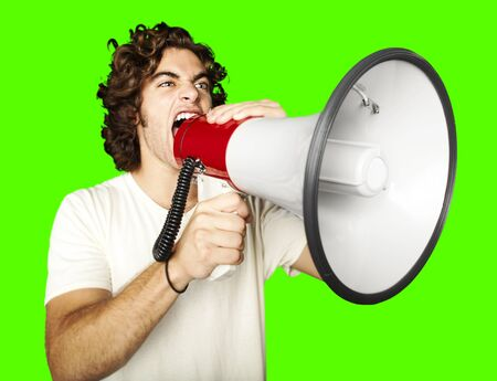 noise isolation: portrait of young man shouting with megaphone against a removable chroma key background