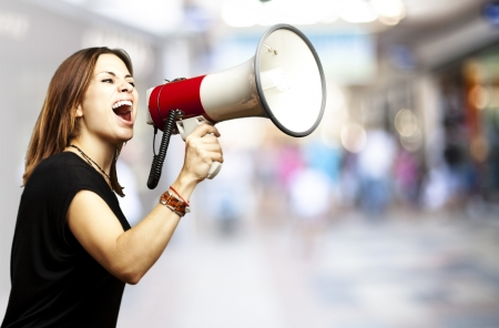 portrait of young woman shouting using megaphone against a crowded place photo