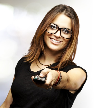 changing channel: portrait of young woman with glasses changing channel with tv control indoor