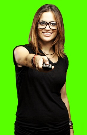 portrait of young woman using tv remote control against a removable chroma key background photo