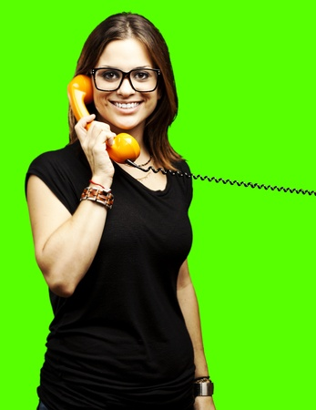portrait of young woman talking on vintage telephone against a removable chroma key background photo