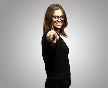 portrait of young woman pointing with glasses over grey background Stock Photo - 11507137
