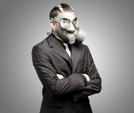 portrait of a business man with gas mask over grey background photo