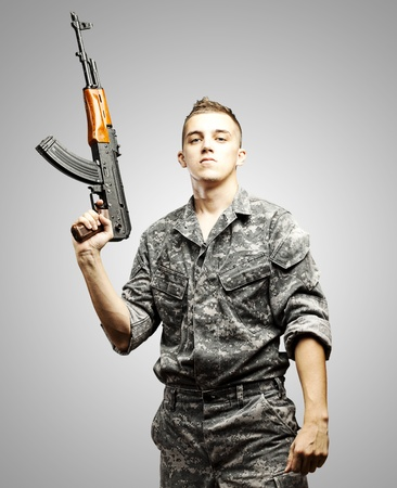 portrait of young soldier holding rifle wearing urban camouflage over grey background photo