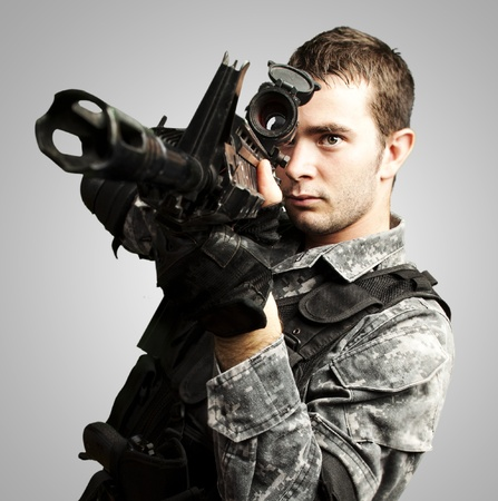 portrait of young soldier aiming with rifle over grey background photo