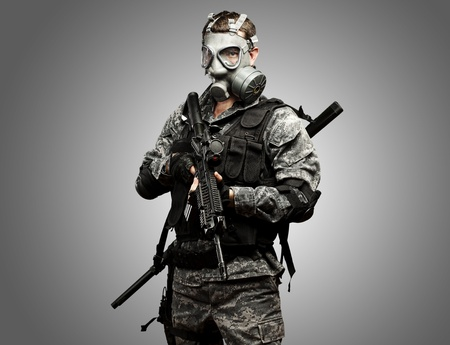 portrait of young soldier with gas mask and rifle against a grey background photo