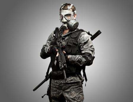 soldado: retrato de joven soldado con m�scara de gas y un rifle sobre un fondo gris Foto de archivo