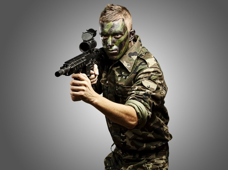 assault rifle: portrait of young caucasian soldier with jungle camouflage over grey background