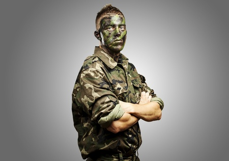 face guard: portrait of young soldier with jungle camouflage paint on a grey background