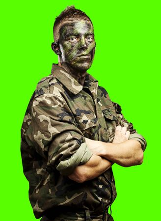 portrait of young soldier painted with jungle camouflage against a removable chroma key background photo