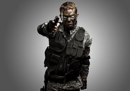 point and shoot: Retrato de soldado furioso con camuflaje urbano que apunta con la pistola sobre fondo gris Foto de archivo