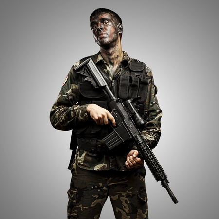 portrait of young soldier painted with jungle camouflage holding riffle over grey background photo