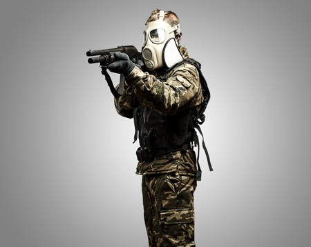 portrait of young soldier with gas mask aiming with shotgun photo