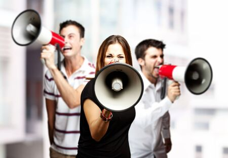 portrait of a angry  group of employees shouting using megaphones against a city background photo
