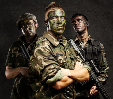 soldier with rifle: portrait of soldiers group with jungle camouflage against a grunge wall