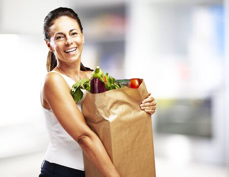 middle aged woman smiling: middle aged woman smiling and holding the purchase indoor Stock Photo