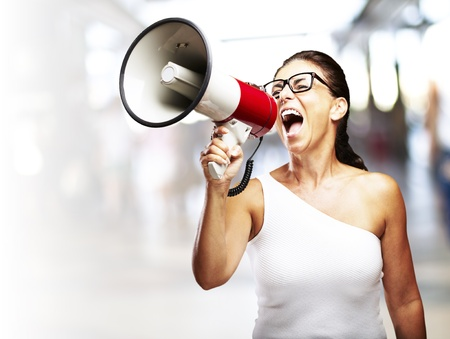 portrait of middle aged woman shouting with megaphone in a crowded place photo