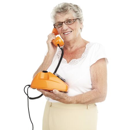 portrait of a happy senior woman talking on telephone over white background photo