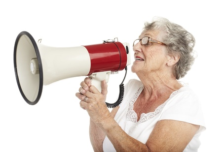 portrait of a happy senior woman shouting with megaphone over white background Stock Photo - 11507121