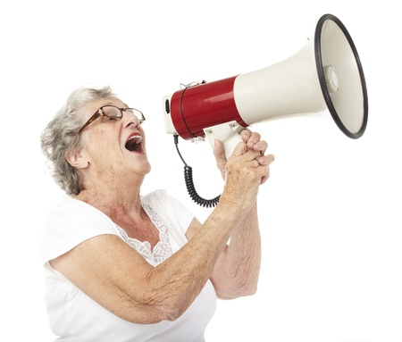 portrait of a happy senior woman shouting with megaphone over white background Stock Photo