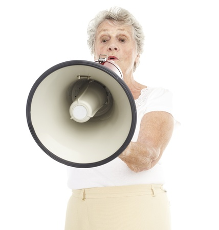 portrait of a happy senior woman shouting with megaphone over white background photo