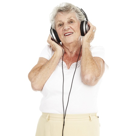 portrait of pretty senior woman listening to music with headphones over white background photo