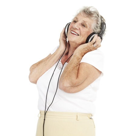 portrait of pretty senior woman listening to music with headphones over white background Stock Photo - 11507419