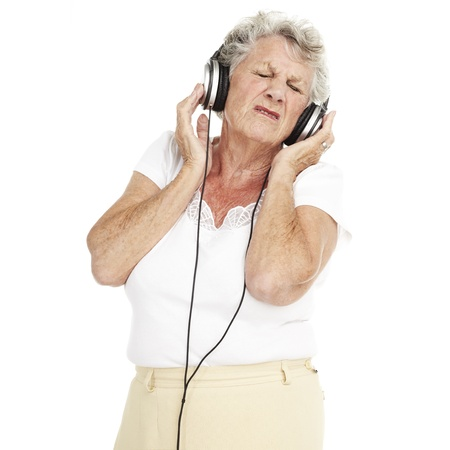 portrait of pretty senior woman listening to music with headphones over white background Stock Photo - 11507322