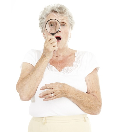 portrait of senior woman looking through a magnifying glass over white background Stock Photo - 11507234