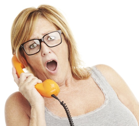 beautiful middle aged woman: portrait of middle aged woman surprised talking on vintage telephone over white
