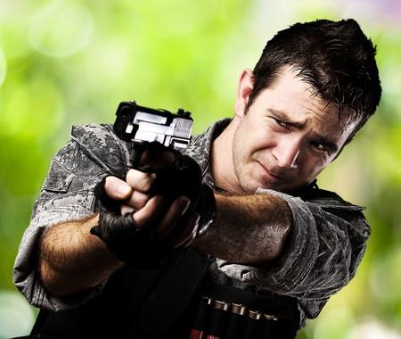hombre disparando: retrato de joven soldado asustado con el objetivo con la pistola sobre un fondo natural