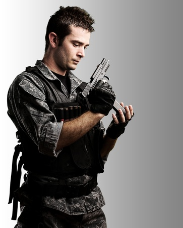 kill: portrait of young soldier reloaing his gun against a grey background