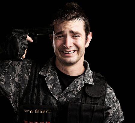 portrait of young soldier suiciding against a black background photo