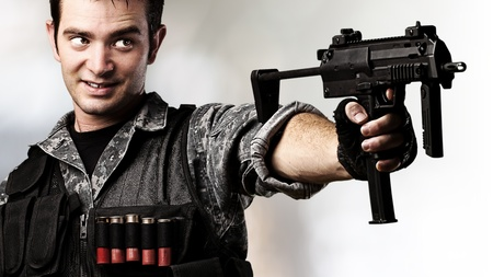 gun room: portrait of young soldier aiming with rifle against a blurred lights background Stock Photo