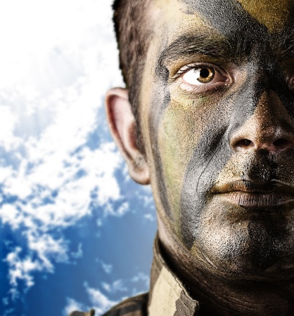 gun control: portrait of young soldier painted with jungle camouflage against a blue sky background