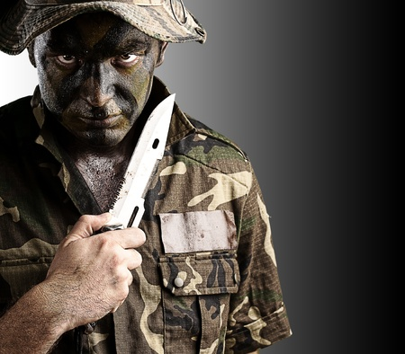 portrait of young soldier with knife and hat against yellow background photo