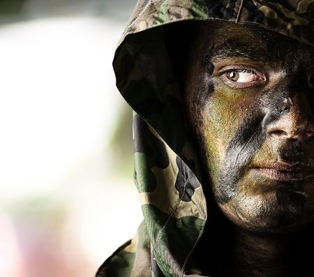 portret van de jonge soldaat gezicht met kap over abstracte achtergrond