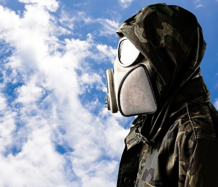 portrait of soldier with gas mask and hood against a cludy sky background photo
