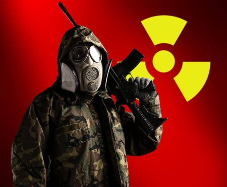 portrait of soldier with rifle and gas mask with radioactive symbol as a background Stock Photo - 11229760