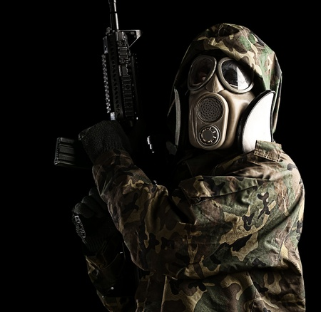iraq war: portrait of young soldier with jungle camouflage and gas mask agains black background