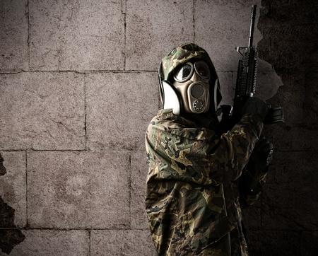 mascara de gas: retrato de un soldado con un rifle y una máscara de gas sobre un fondo grunge