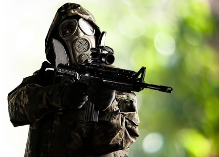 portrait of soldier with gas mask aiming with rifle against a nature background Stock Photo - 11232255