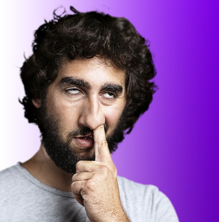 bad hygiene: portrait of young man with the finger on his nose against a purple background