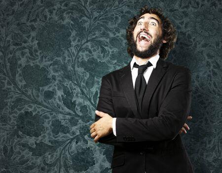 dientes sucios: Retrato de hombre joven riendo contra la pared del grunge Foto de archivo