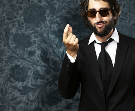 portrait of young business man gesturing money against a vintage wall Stock Photo - 11497069